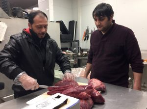 Abdul, a Syrian refugee who arrived in Madison last month, demonstrates his butchering skills while Istanbul Market owner Yashar Tairov looks on. Tairov, who emigrated from Russia, said refugees such as Abdul are hard working and pose no threat to the country. Abdul and his family arrived a week before President Donald Trump issued an indefinite ban on Syrian refugees. (Photo by Dee J. Hall, WCIJ, taken on Jan. 31)