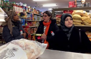 Rihab Taha, left, a caseworker for Jewish Social Services who came as an immigrant from Sudan; Becca Schwartz, resettlement coordinator for JSS; and Rula, a newly arrived refugee from Syria, shop at Istanbul Market in Madison on Jan. 31. Rula and her family came to Madison one week before President Donald Trump indefinitely halted all refugee immigration from Syria. (Photo by Dee J. Hall, WCIJ)